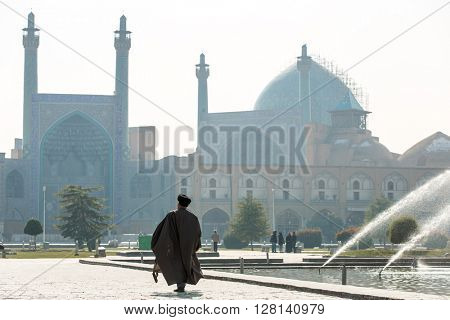 Esfahan, Iran - December 13, 2015: Unidentified Mullah walk towards the Shah Mosque in Isfahan, Iran.