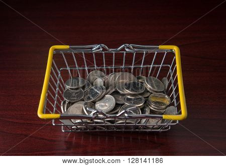 Many one dirham coins in a shopping basket - A concept