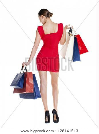 Fashion woman portrait isolated. White background. Happy girl hold shopping bags. Red dress. female beautiful model