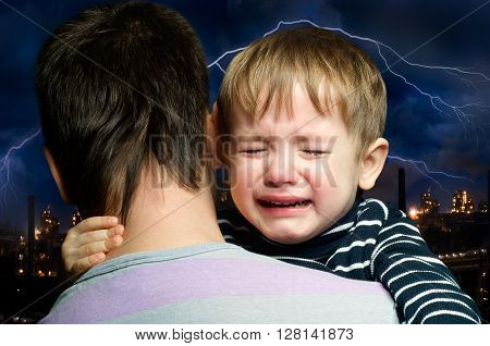 Crying child in the hands of  father on the background of lightning