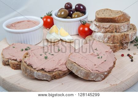 Homemade pate olives tomatoes and slices of bread on wooden board