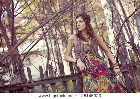 Hippie girl standing against the vintage fence.