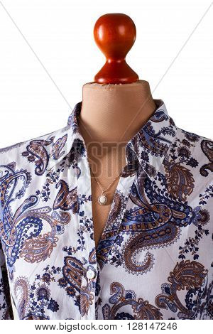 Dark floral shirt and pendant. Necklace and shirt on mannequin. Woman's trendy flower pattern shirt. Brand new shirt and accessory.