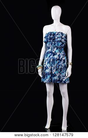 Short blue summer dress. Mannequin wearing short floral dress. Trendy dress on black background. Woman's brand new summer clothing.