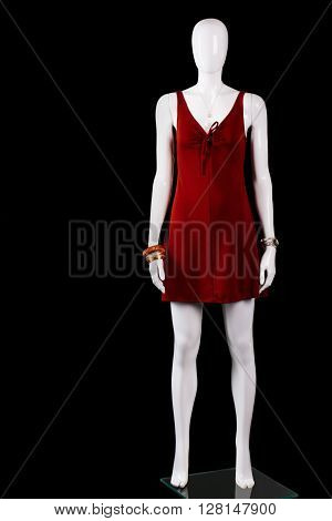 Red keyhole dress with accessories. Short red dress on mannequin. Woman's garment made of stretch. Fashionable dress in stock.