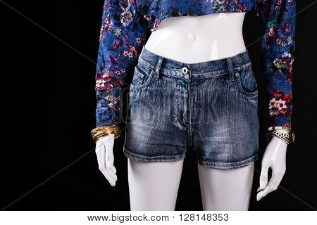 Denim shorts, watch and bracelet. Female mannequin wearing denim shorts. Woman's brand new summer shorts. Quality clothes at low price.
