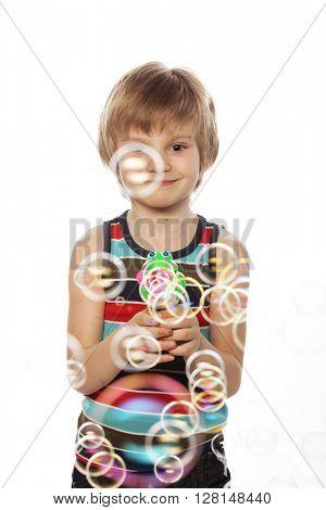 little caucasian boy blowing soap bubbles on white background, front view