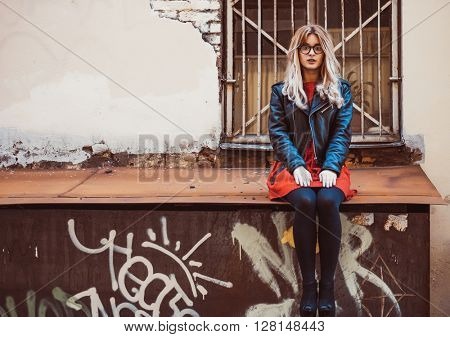 young blond woman wearing red dress posing in the city