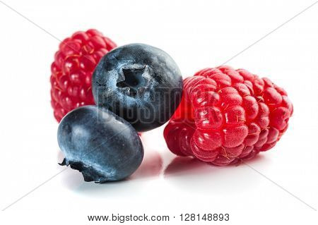 Extreme close-up image of blueberries and raspberries on white background