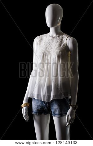 White sleeveless top and shorts. Shorts and top on mannequin. Woman's fashionable summer outfit. Simplicity and beauty.