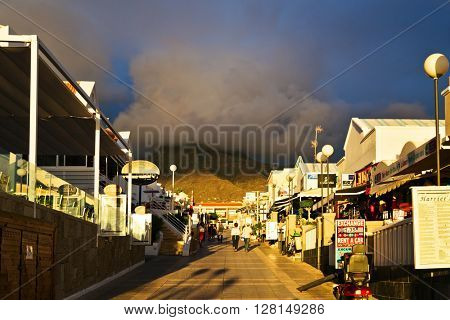 TENERIFE ISLAND, SPAIN - OCTOBER 28, 2015 : Alley near the sea with small shops and restaurants in the rays of the setting sun in Costa Adeje, Canary Islands