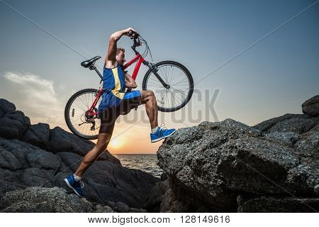 Man carrying a bike on the shoulder on the rock during sunset