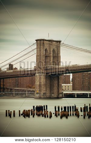 Brooklyn Bridge and abandoned pier ruins in East River.