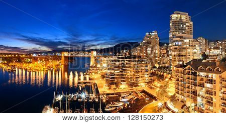 Vancouver harbor view with urban apartment buildings and bay boat at dusk in Canada.