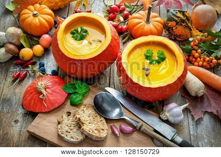 Pumpkin soup in the open pumpkins on a wooden table
