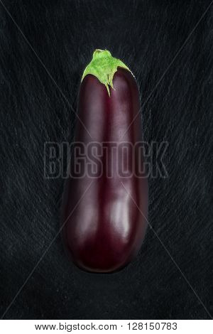 Fresh eggplant on a black slate background. Top view