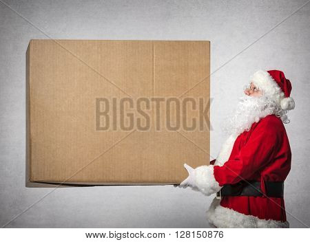 Santa Claus holds a big gift box with copy space for your text