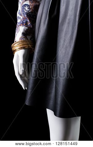 Black skirt and gold bracelet. Mannequin's hand with golden bracelet. New exclusive accessory for women. Stylish and expensive.