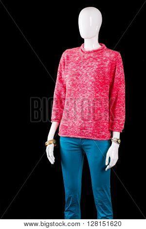 Pink sweater and truquoise pants. Mannequin wearing pants and sweater. Girl's trendy spring outfit. Colorful clothing of high quality.