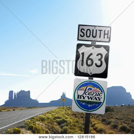Sign for Scenic Byway 163 south beside road with rock formations in background in Monument Valley, Utah.