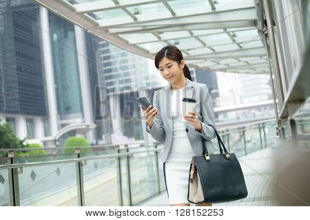 Business woman walking with cell phone