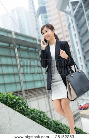 Business woman smiling with cell phone outside office building