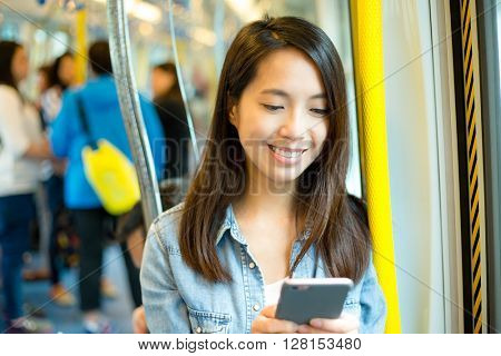 Woman using cellphone in train compartment