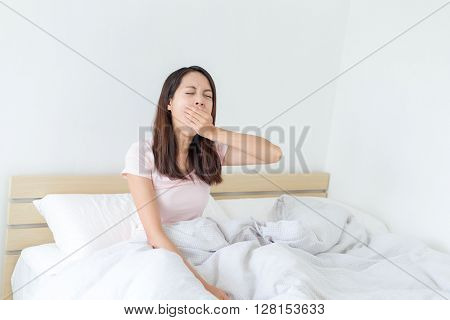 Young woman sitting on the bed and yawning