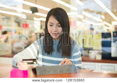 Woman using credit card and touch pad for online booking ticket