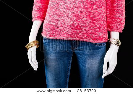 Pink sweater, jeans and accessories. Mannequin wearing jeans and accessories. Lady's high-quality denim pants. Bright and fashionable clothes.