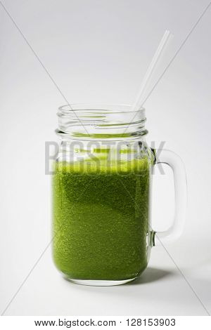 Healthy green smoothie with straw in a jar mug on white  - superfoods, detox, diet, health, vegetarian food concept