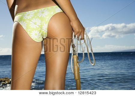 Close up of derriere of Asian Filipino young adult female holding jump rope in swimsuit on beach in Maui Hawaii.