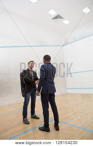 Two businessmen shaking hands before having match in squash. Happy men inbusiness suits on squash court.