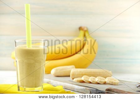 Banana cocktail and fresh bananas on wooden background