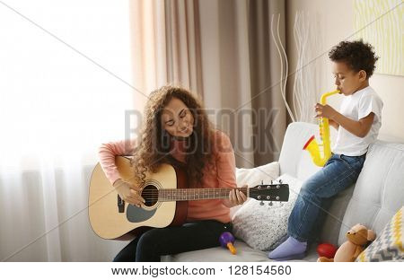 Little boy and a young girl playing on guitar in living room.