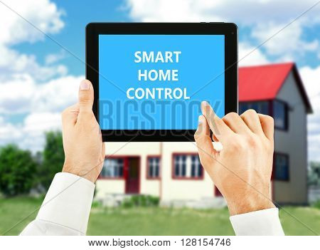 Smart home control concept. Tablet pc in hands on house background