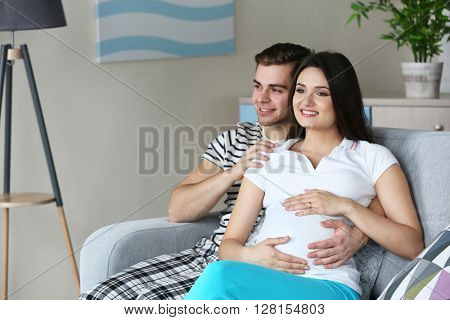 Pregnant woman with husband sitting on sofa in the room