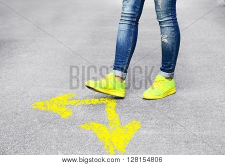 Female feet walking on road with yellow arrows