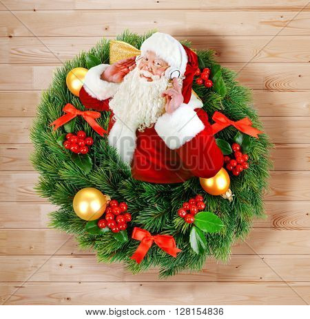 Santa Claus appearing from Christmas wreath