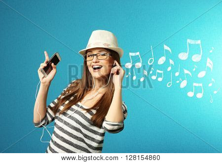 Young woman listening to music and singing against blue background