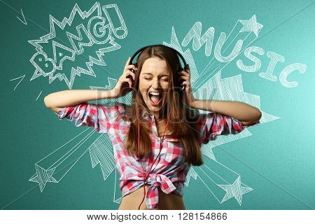 Young woman listening to music and signing loud against turquoise background