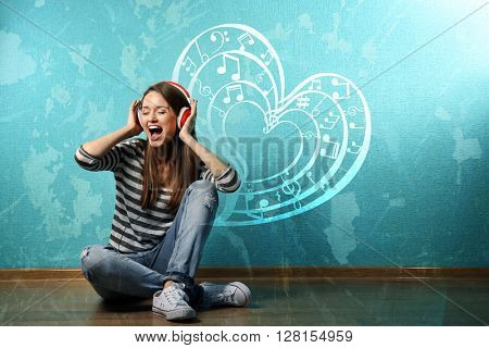 Young woman sitting on floor and listening to music against blue wall. Love music concept