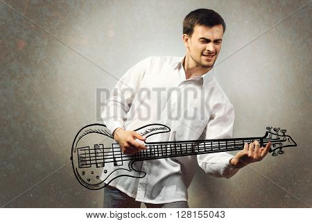 Handsome young man pretending to play guitar against gray background
