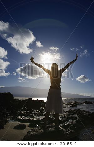 Young adult Asian Filipino female stretching arms in air on beach in Maui Hawaii.