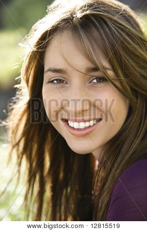 Close-up portrait of attractive young Caucasian woman with long brown hair smiling at viewer.