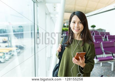 Woman listen to music on mobile phone in airport
