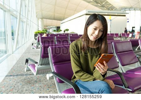 Woman on smart phone at gate waiting in terminal