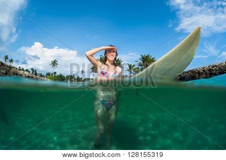 Underwater split shot of the young lady standing with surf board
