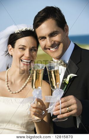 Caucasian mid-adult bride and groom toasting champagne looking at viewer and smiling.