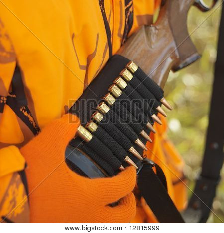 Close-up of hunter removing bullet from ammo holder on rifle.